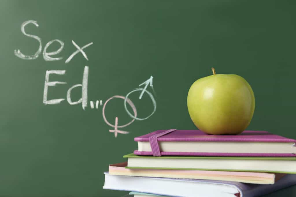 "Books and apple near chalkboard with phrase ""Sex ed"""
