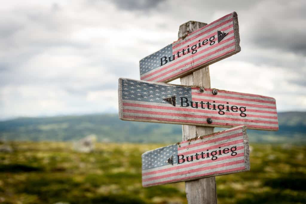 Buttigieg text on wooden american flag signpost outdoors in nature.