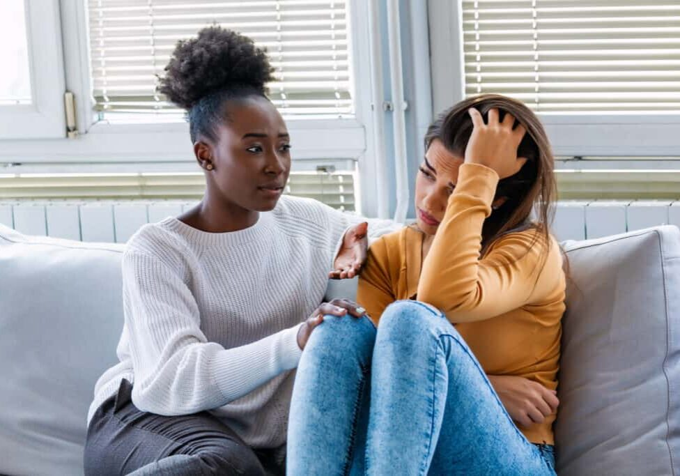 Sad girl and supporting friends trying to solve a problem. Two sad diverse women talking at home. Female friends supporting each other. Problems, friendship and care concept