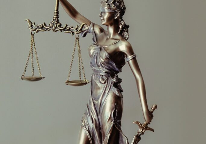 woman in gold dress holding sword and scales of justice